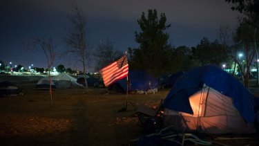 Homeless tents are pitched around an America flag along the Santa Ana River trail in Anaheim, California.