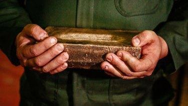 A worker carries a 28-kilogram gold bar.