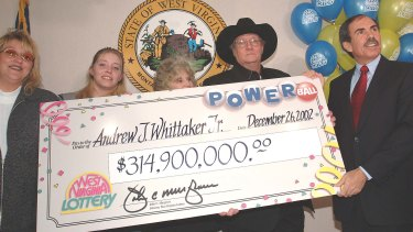 "Andrew ""Jack"" Whittaker, jnr (black hat) with a cheque for $314.9 million won in a Christmas Day jackpot in 2002."