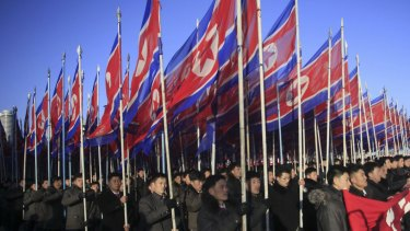 North Koreans parade with the North Korean flag in Kim Il-sung Square in Pyongyang, North Korea.
