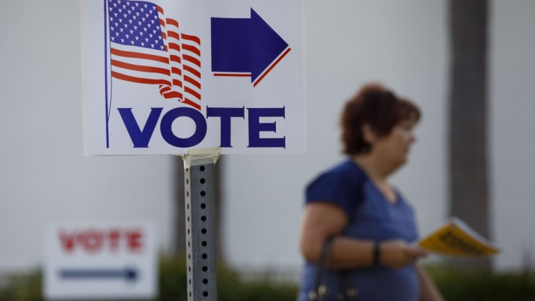"""A """"Vote"""" sign is displayed as a resident enters a polling place on Lido Isle in Newport Beach."""