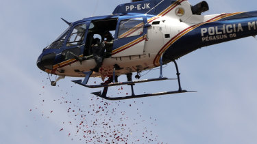 A helicopter releases flower petals on top of an iron ore mining complex to pay homage to the 110 victims killed and 238 who are still missing after a mining dam collapsed in Brumadinho, Brazil.