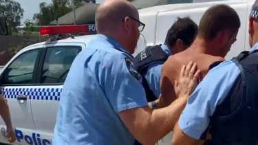 Police arresting the man after he allegedly stabbed two officers.
