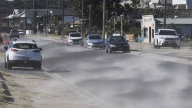 Wind-blown sand streams down Prince Charles Parade in Kurnell last month.