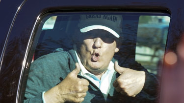 President Donald Trump gives two thumbs up to supporters outside his golf club after losing the presidential election.
