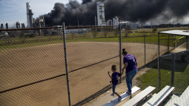 Cloud of smoke in the background from the TPC Group Port Neches Operations explosion is visible from a little league baseball park.