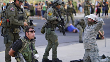 Albuquerque police detain members of the New Mexico Civil Guard, an armed civilian group, following the shooting of a man during a protest over a statue of a conquistador.
