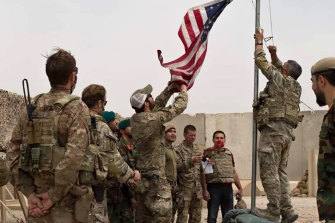 The US flag is lowered as American and Afghan soldiers attend a handover ceremony at Camp Anthonic in Helmand province.