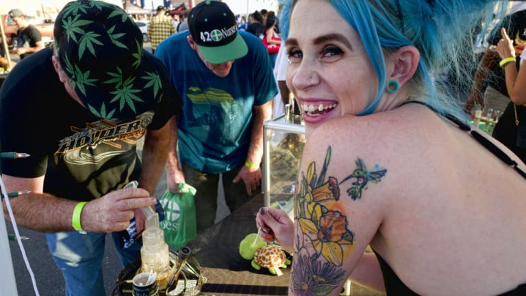 Bud tender Kansas, right, offers up a puff of cannabis concentrates at the Turtle Puddles' booth at the cannabis-themed Kushstock Festival at Adelanto, California.