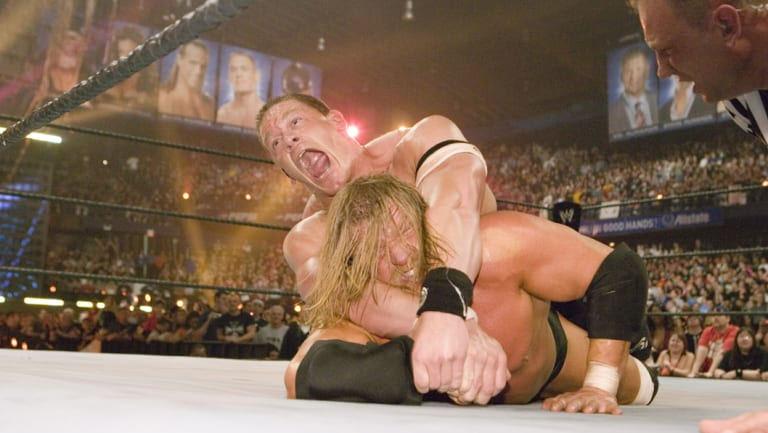 John Cena and Triple H grapple at Wrestlemania 22 in 2008.