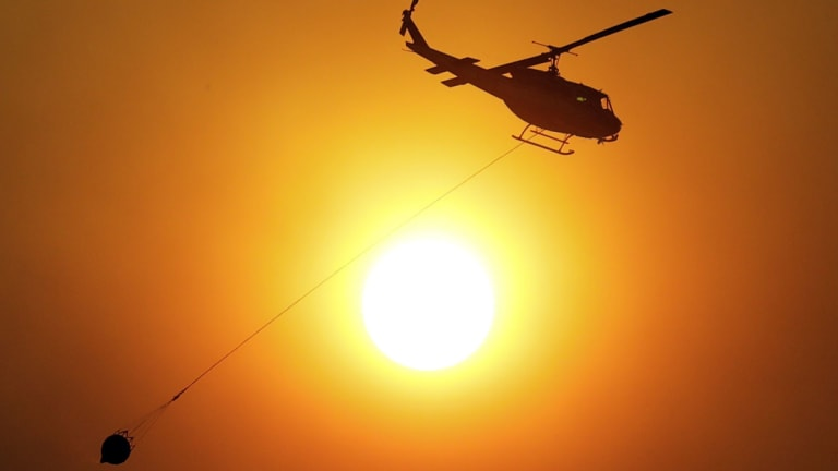 A helicopter carries water to drop on an advancing wildfire near Finley, California.