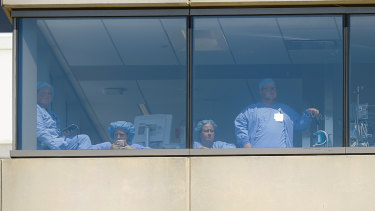 Medical personnel watch a protest against the arrival of President Donald Trump outside their hospital in Dayton.