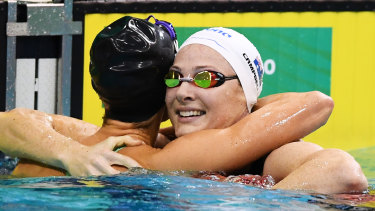 Emma McKeon hugs second place Cate Campbell in the 100m freestyle.