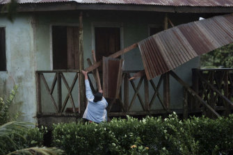 A woman works to recover a roof part damaged by hurricane Eta in Wawa, Nicaragua.