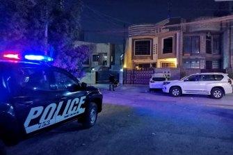 Police outside the home of Hisham al-Hashimi, where he was shot.