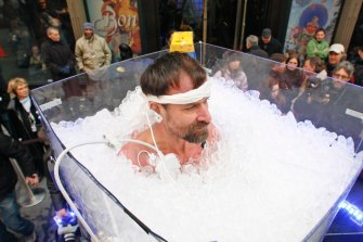 Wim Hof stands upright in a tub of ice during one of his record attempts.