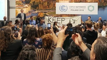 Protesters take over a stage to protest a pro-coal event at the COP24 climate talks in Katowice, Poland.