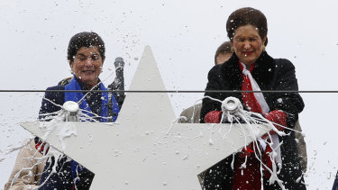 Luci Baines Johnson, left, and her sister, Lynda Johnson Robb, smash champagne bottles to christen the Lyndon B. Johnson, the third Zumwalt-class guided missile destroyer, built at Bath Iron Works.