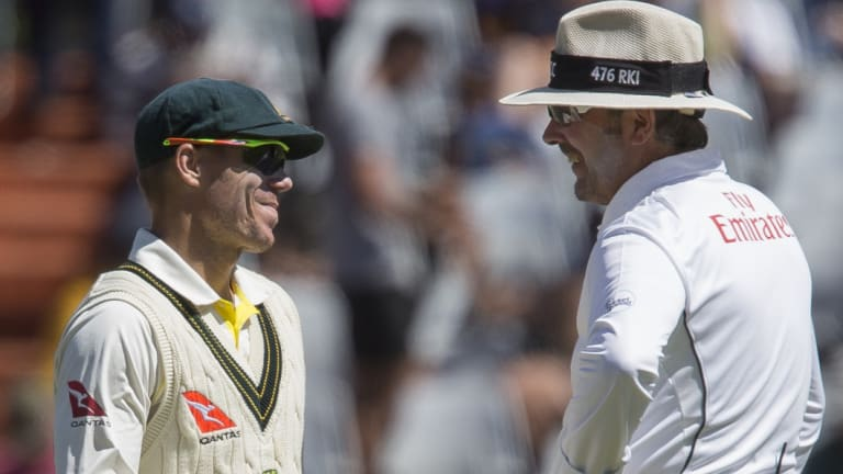 David Warner talks to an umpire on the fourth day of the third Test in Cape Town.