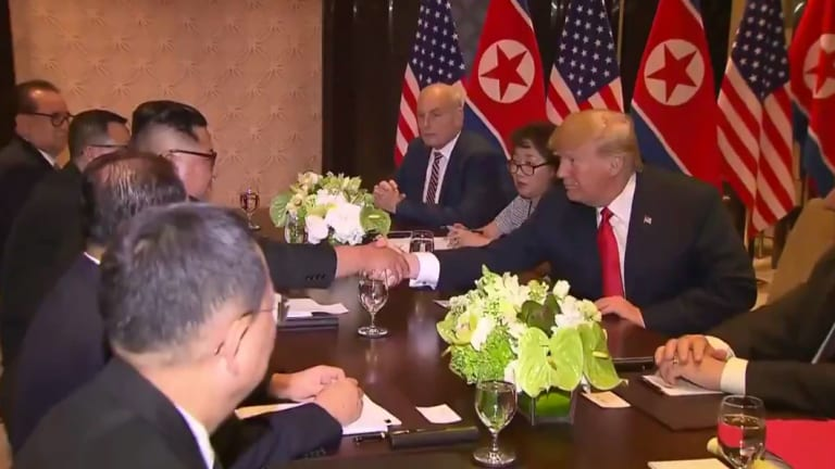 Trump and Kim shake hands with their advisers by their sides.