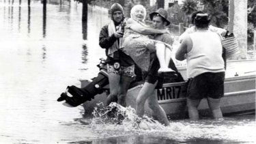 Helpful hands ... rescuers carry an elderly woman to safety during the flood that devastated Brisbane in 1974.