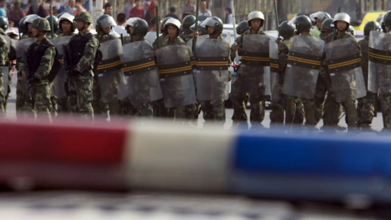 Chinese paramilitary police close off a road after riots in Urumqi, western China's Xinjiang province.