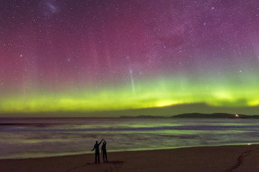 A couple in silhouette dancing on a beach under an incredible bright green display of the Aurora Australis or Southern Lights over a beach in Tasmania with bright blue bioluminescence in the waves caused by Noctiluca scintillans. Southern Lights images  Supplied/Getty One time use for Traveller only Belinda Jackson story