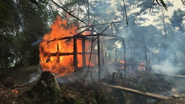 Houses on fire in Gawdu Zara village, northern Rakhine state, Myanmar, where where pages from Islamic texts were seen ripped and left on the ground in 2017.