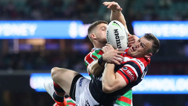 Brett Morris of the Roosters and Adam Doueihi of the Rabbitohs compete for the ball.