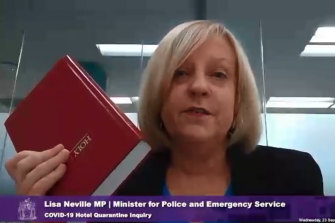 Lisa Neville taking an oath on the Bible before giving evidence at the hotel quarantine inquiry.