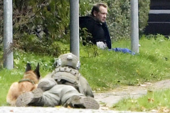 A police office watches Peter Madsen as he sits on the side of a road after being apprehended.