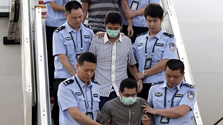 The long reach of Operation Fox Hunt: six accused fugitives are taken back to China under escort from Indonesia in June 2015.