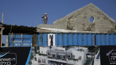A Palestinian works on a new housing project in the West Bank settlement of Naale.