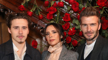 Victoria Beckham, flanked by her son Brooklyn and husband David.