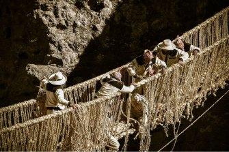 Members of the Huinchiri community rebuild an Incan hanging bridge, known as the Q'eswachaka bridge, using traditional weaving techniques in Canas, Peru.