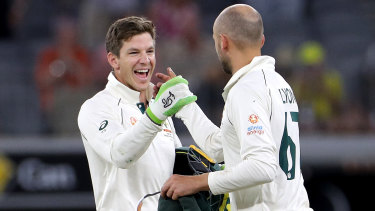 Tim Paine and Nathan Lyon celebrate victory on night four.