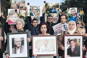 Syrian activist Noura Ghazi (centre) with a picture of her husband Bassel Khartabil at a ''Families for Freedom'' demonstration outside the UN's office in Geneva in February 2017.