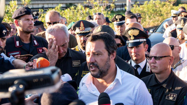 Matteo Salvini, Italy's deputy prime minister, centre, speaks to the media as he visits the Morandi motorway bridge after it partially collapsed in Genoa, Italy.