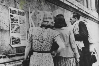 German civilians in Munich look at a poster displaying pictures of atrocities at Nazi death camps under the heading 'Whose guilt?'.