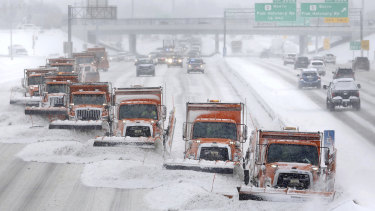 Snow plows move along a highway in Madison, Wisconsin.