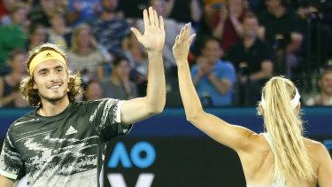 Stefanos Tsitsipas of Greece high fives Caroline Wozniacki of Denmark.