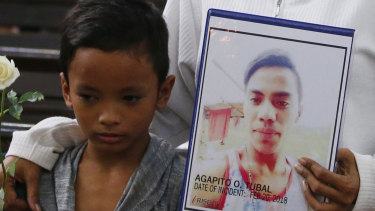 A boy stands next to his mother, who holds a portrait of his brother, an alleged victim of President Rodrigo Duterte's 'war on drugs', during a religious service in Manila in 2018.