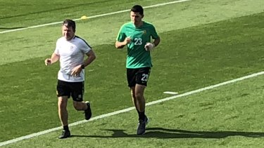 Battling: Tom Rogic trains with a bandage on his broken hand in Dubai on Tuesday.