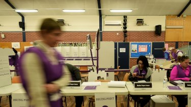 Australian electoral commission staff prepare for voters to arrive minutes before the Blacktown South Public School opens so people can vote in the Australian Federal election in 2016