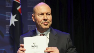 Treasurer Josh Frydenberg poses for photos with budget papers before delivering his post-budget address to the National Press Club.