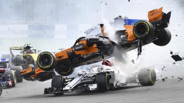 Spectacular: Fernando Alonso's McLaren flies over Sauber's Charles Leclerc in Belgium.