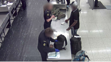 ABF officials search the man at Perth International Airport.
