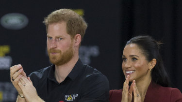 Britain's Prince Harry, the Duke of Sussex and his wife Meghan, the Duchess of Sussex are seen during the medal presentation following the Wheelchair Basketball Final.
