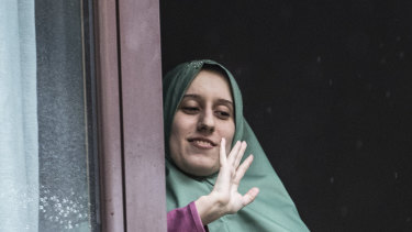 Silvia Romano gestures from a window after she arrived at her home, in Milan.