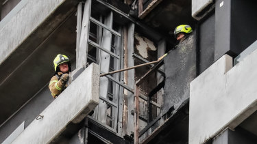 Firefighters inspect the damage at the Neo200 tower.